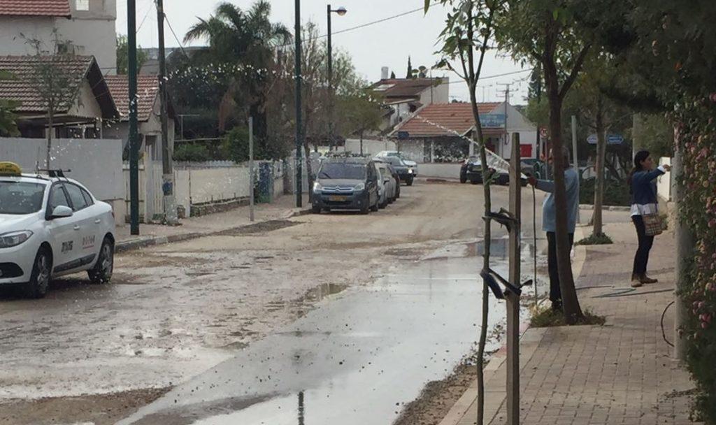 התושבים מרטיבים את הכביש בעצמם בשכונת עלייה. צילום:עולמית עקבי כהן