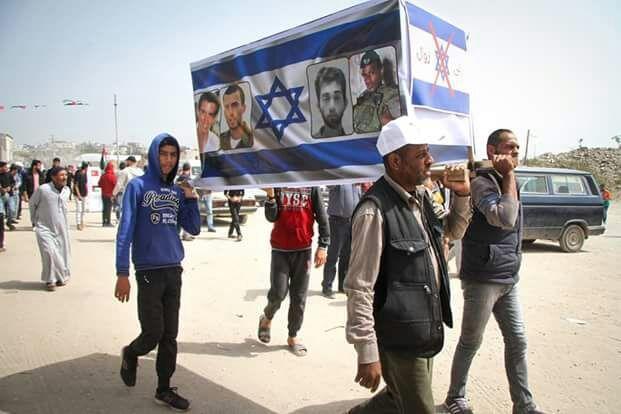 תמונות החטופים על ארון קבורה בהפגנה בעזה