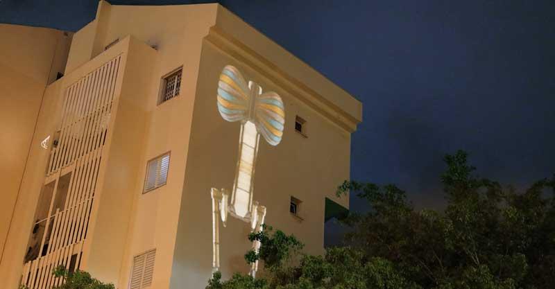 עבודת אמנות של נאוה ג'וי אוזן מוקרנת על קיר הבניין בהדרים. צילום באדיבות האמנית