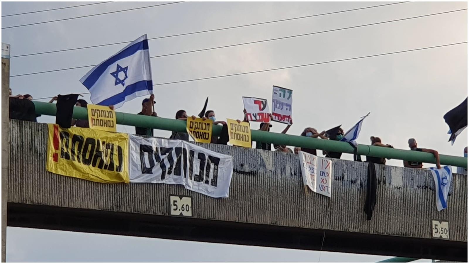 מחאת הדגלים השחורים בגשר רשפון מעל כביש החוף